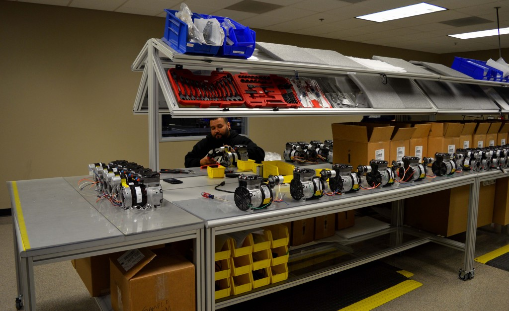 Production worker works efficiently surrounded by the necessary tools to complete the project